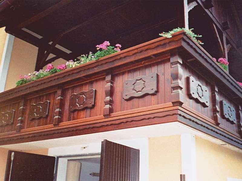 Lesena ograja z okrasnimi lesenimi tablami na balkonu